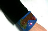 a felt bracelet with a circuit sewn with conductive thread which lights a small LED bulb